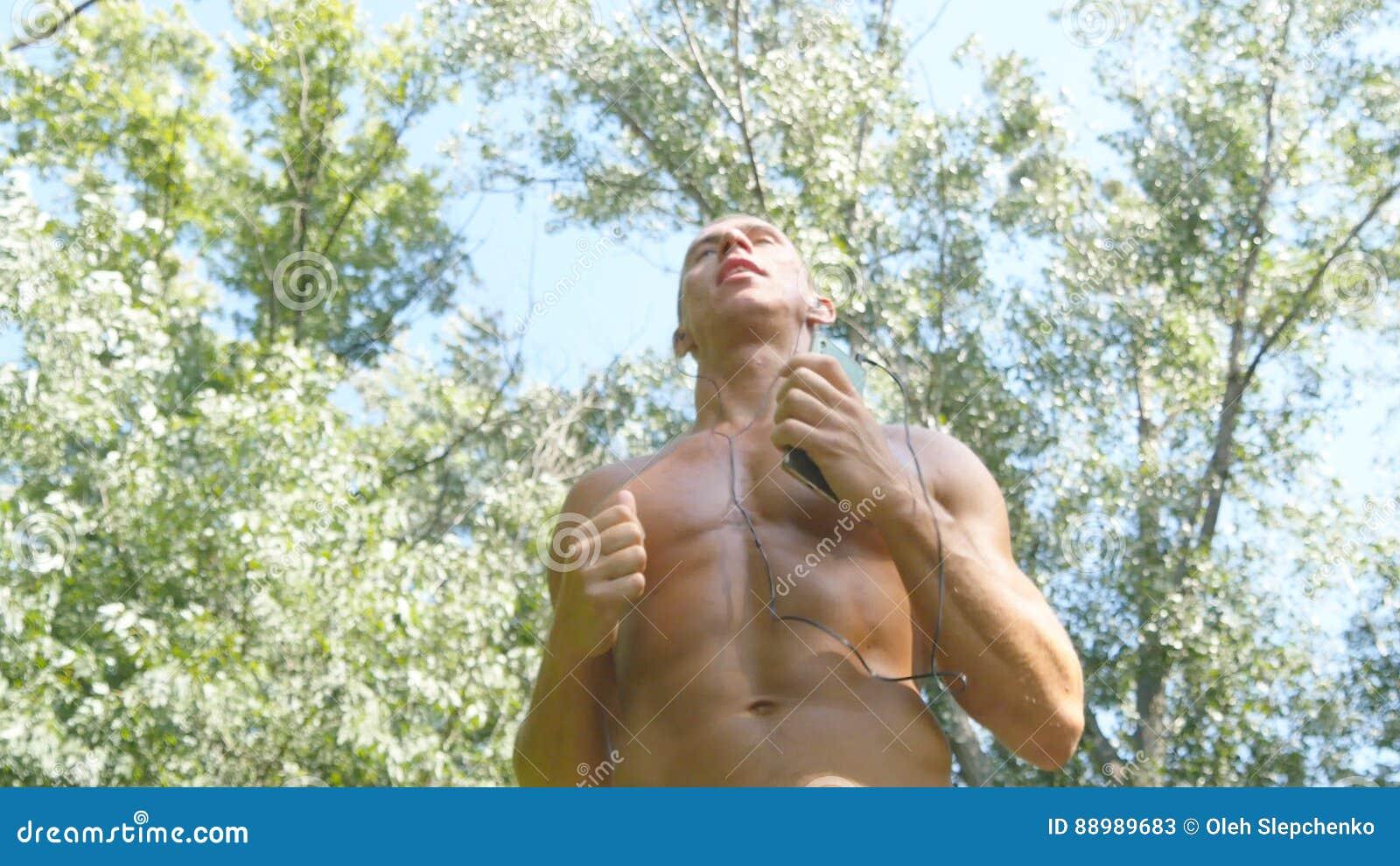 Jeune athlète musculaire courant au chemin forestier Homme fort actif s exerçant dehors Mâle sportif beau convenable
