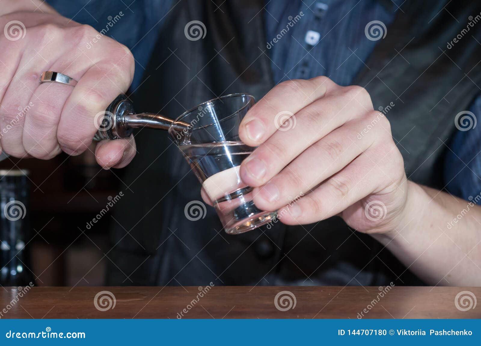Jeune barman beau dans la chemise bleue, le gilet noir et l arc rouge donnant le verre avec le cocktail rouge d alcool
