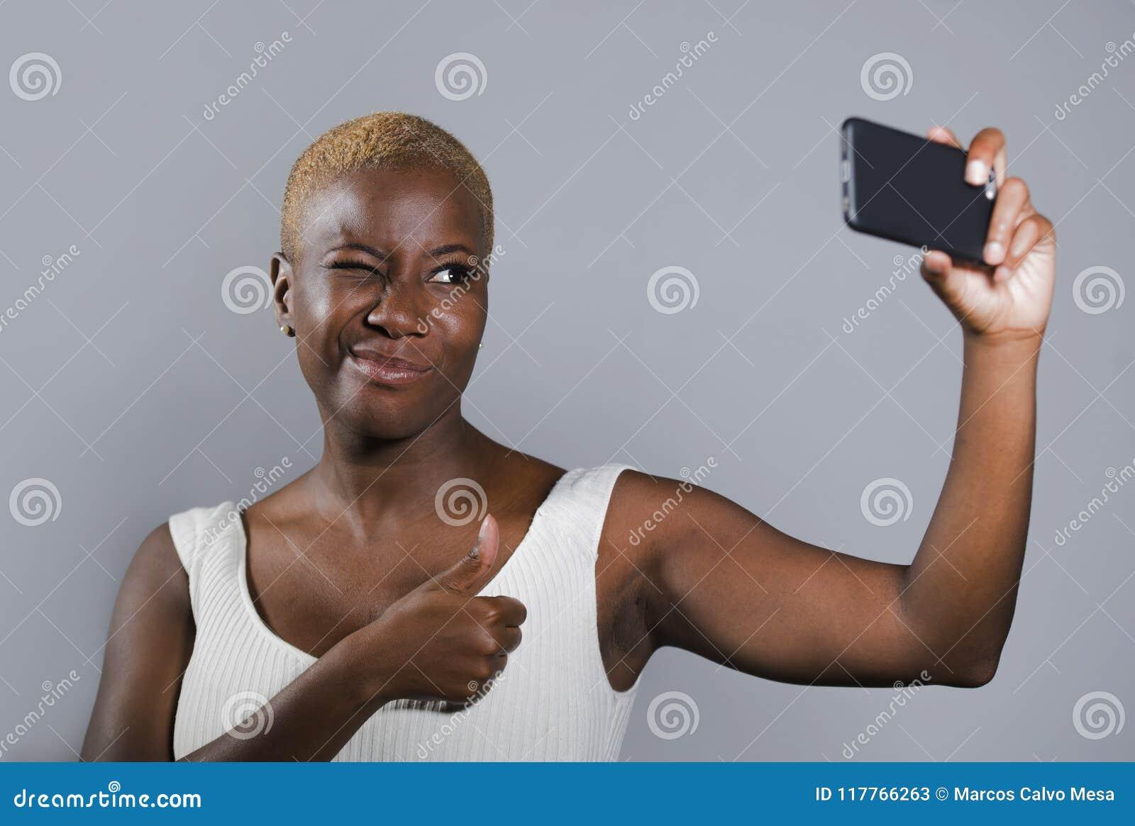 Jeune beau et heureux sourire afro-américain noir de femme excité prenant le portrait de photo de selfie avec le téléphone portab