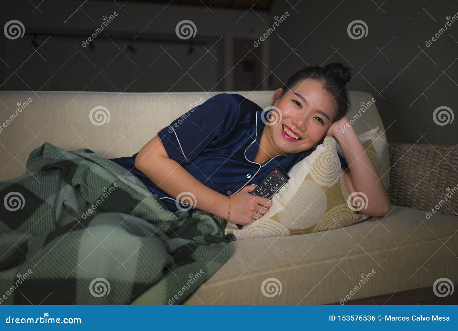 Jeune beau se reposer chinois asiatique heureux et décontracté de salon de femme à la maison confortable sur l épisode de observa