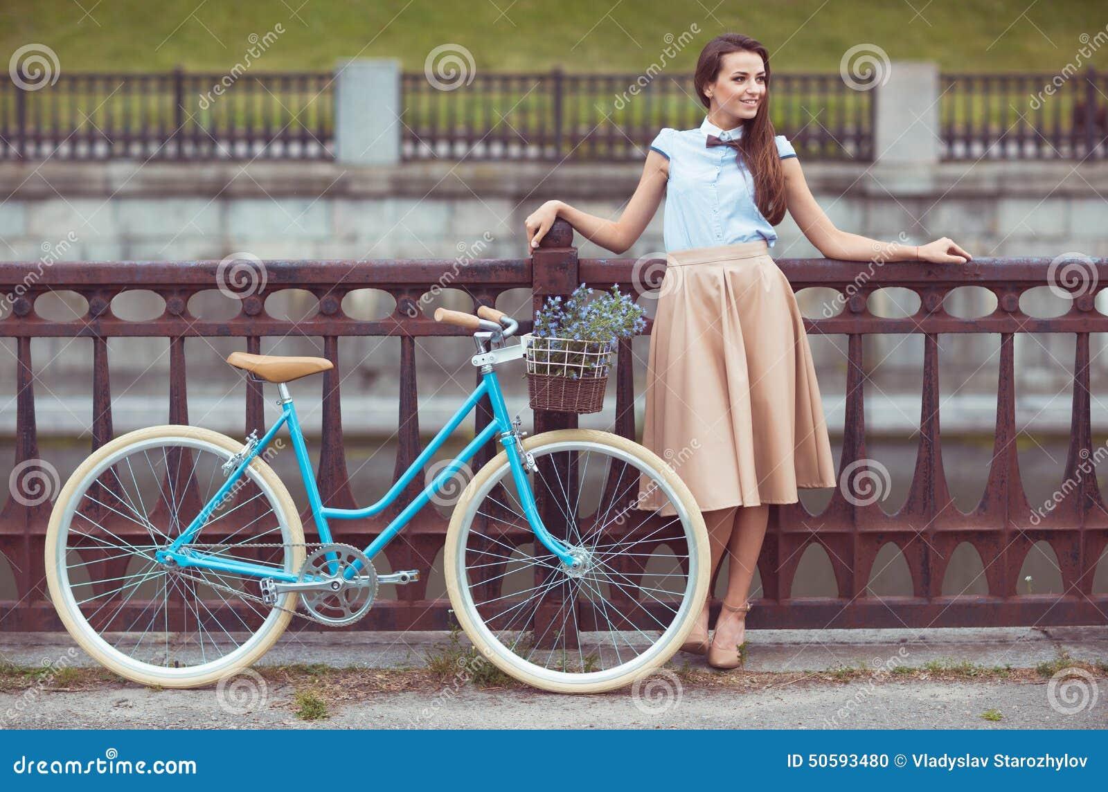 Jeune belle, d une manière élégante habillée femme avec la bicyclette