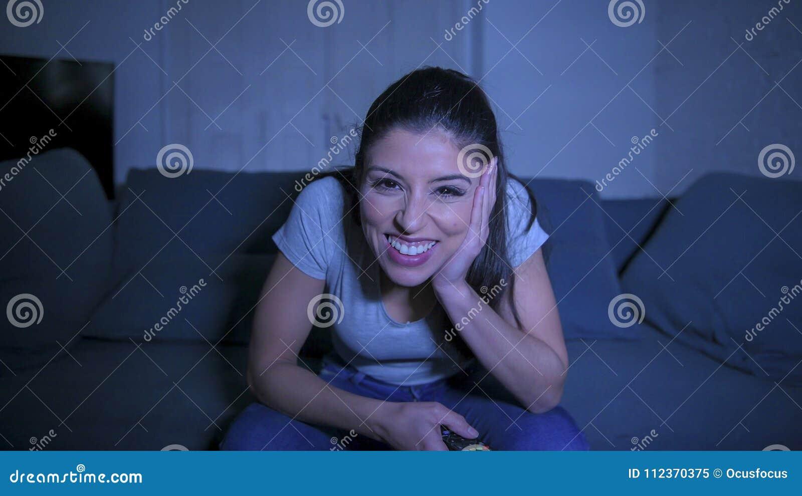 Jeune belle et heureuse femme latine sur son 30s tenant l extérieur de TV appréciant à la maison le programme télévisé de observa