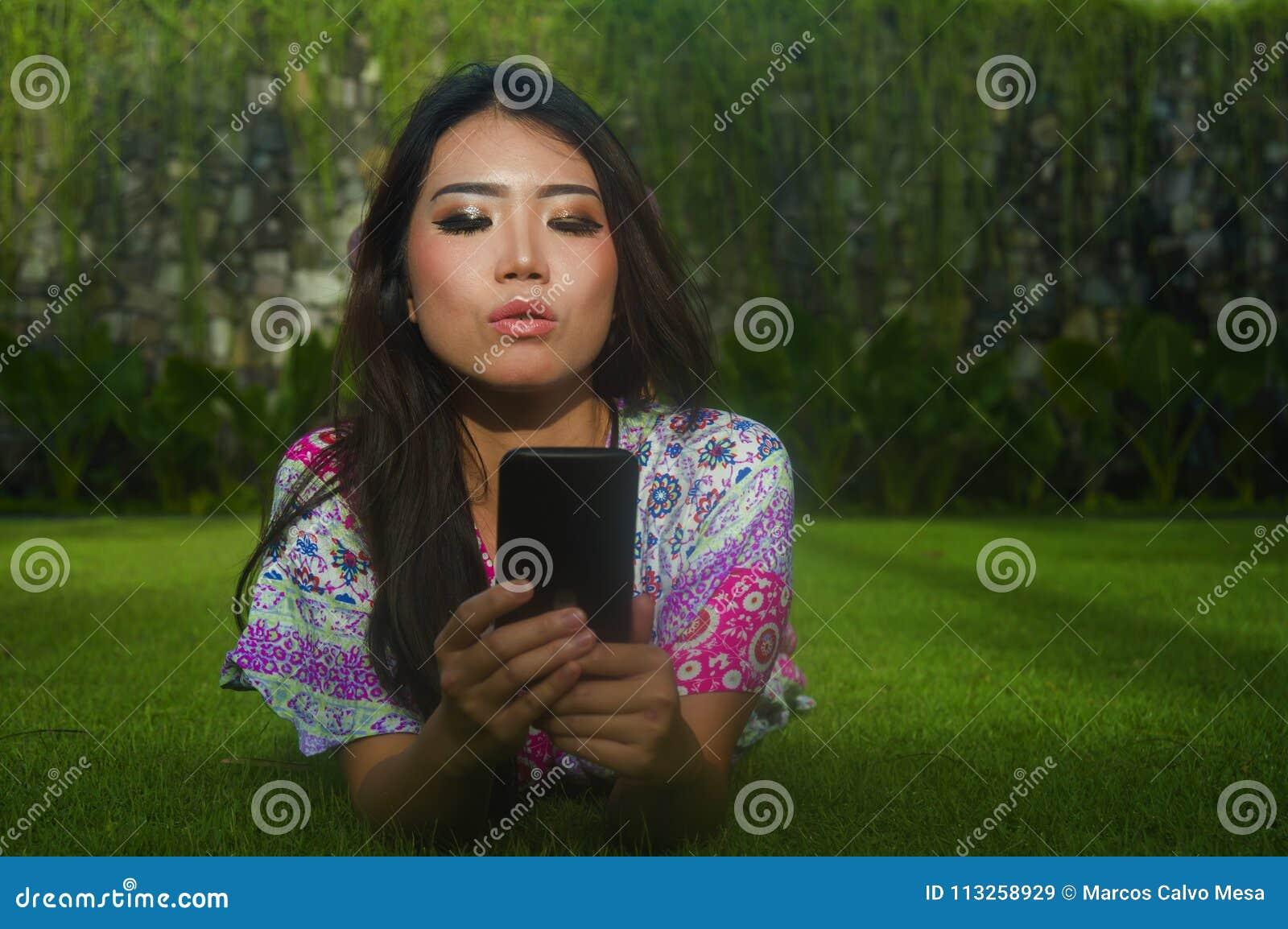Jeune belle et magnifique femme chinoise asiatique attirante se trouvant sur le parc d herbe verte utilisant le media social APP