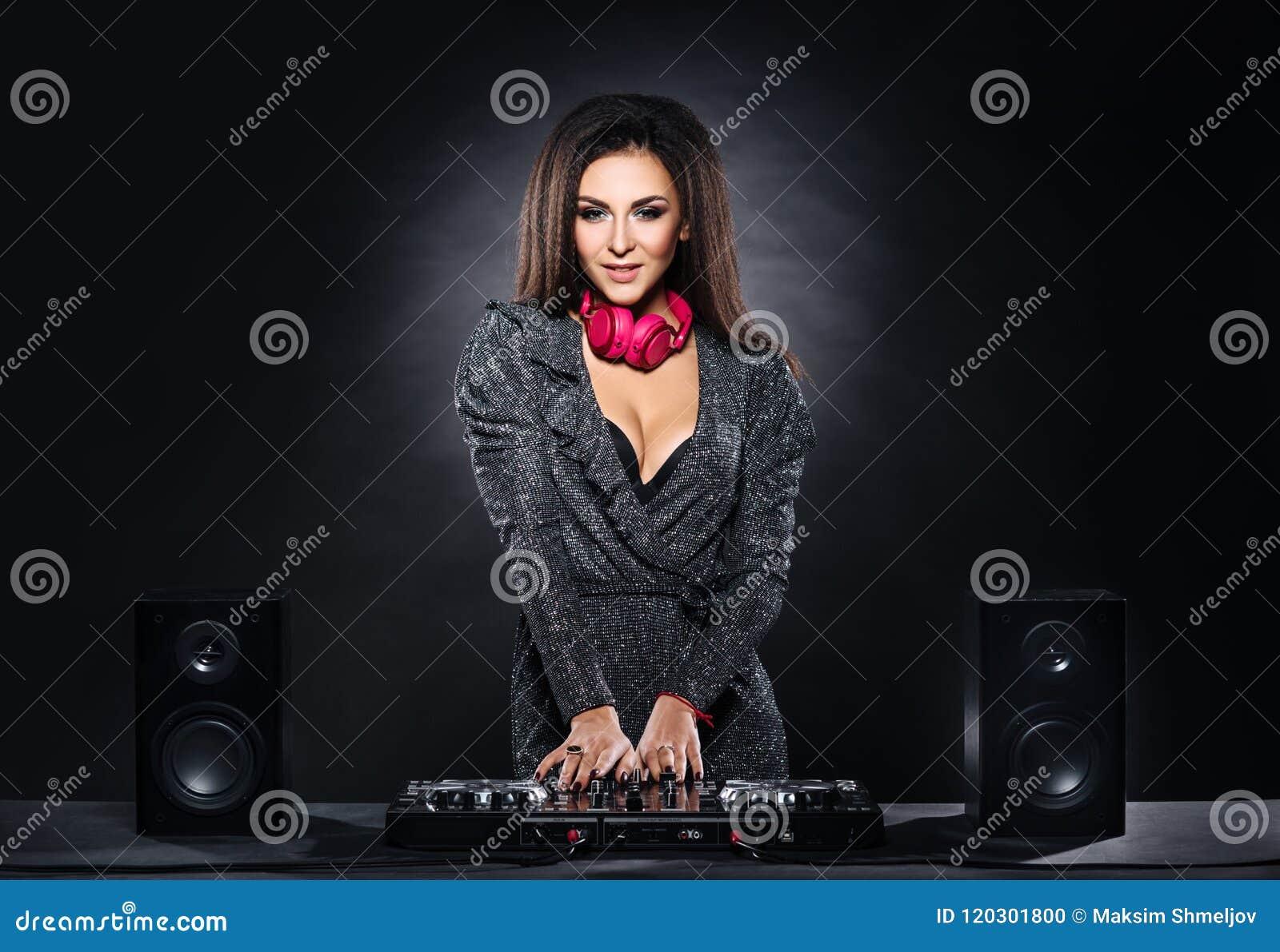 Jeune, belle et sexy fille du DJ jouant la musique sur une partie de disco dans une boîte de nuit