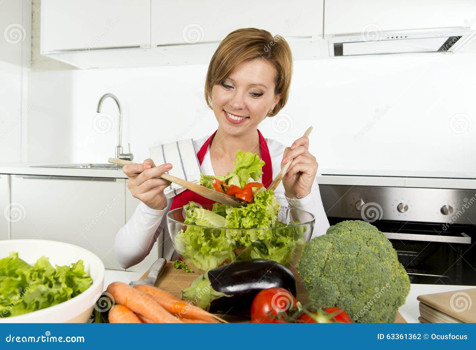 Jeune belle femme à la maison de cuisinier à la cuisine moderne préparant le sourire végétal de saladier heureux