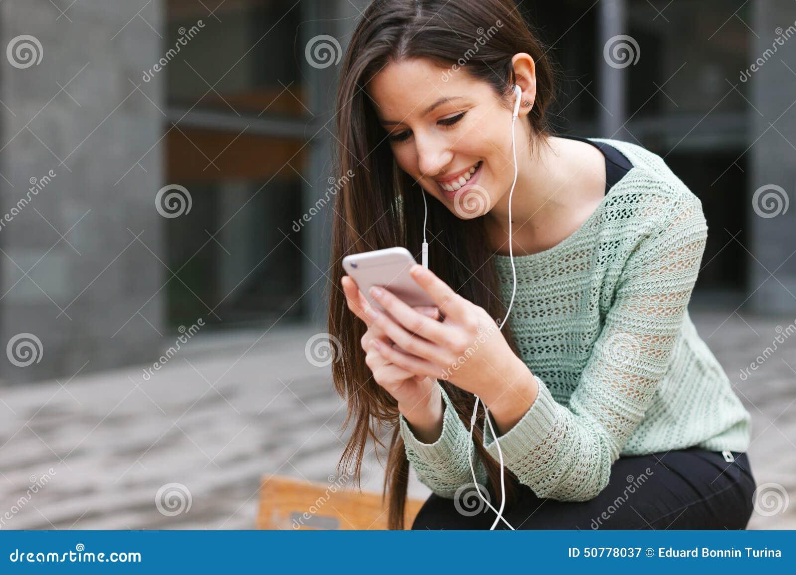 Jeune belle femme écoutant la musique avec le téléphone dedans dehors