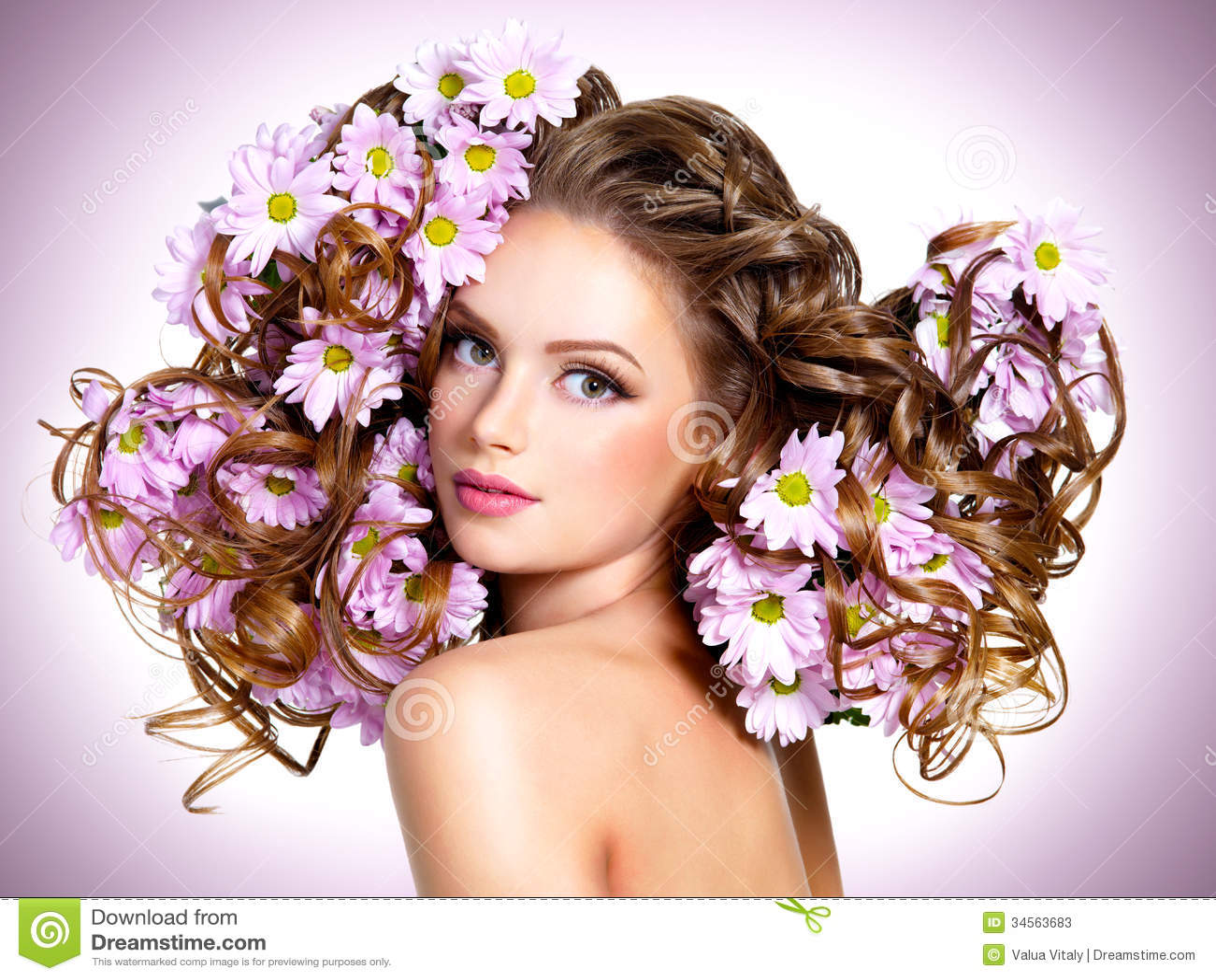Jeune belle femme avec des fleurs dans des poils