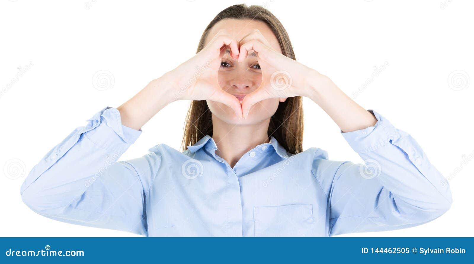 Jeune belle femme avec des mains disposées dans le signe de forme de coeur