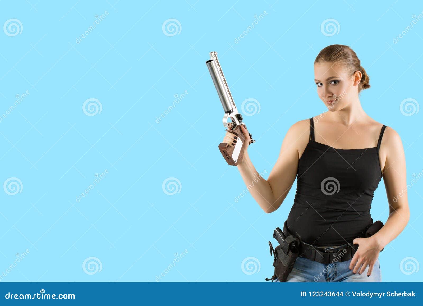 Jeune belle femme blonde sexy jugeant le pistolet disponible