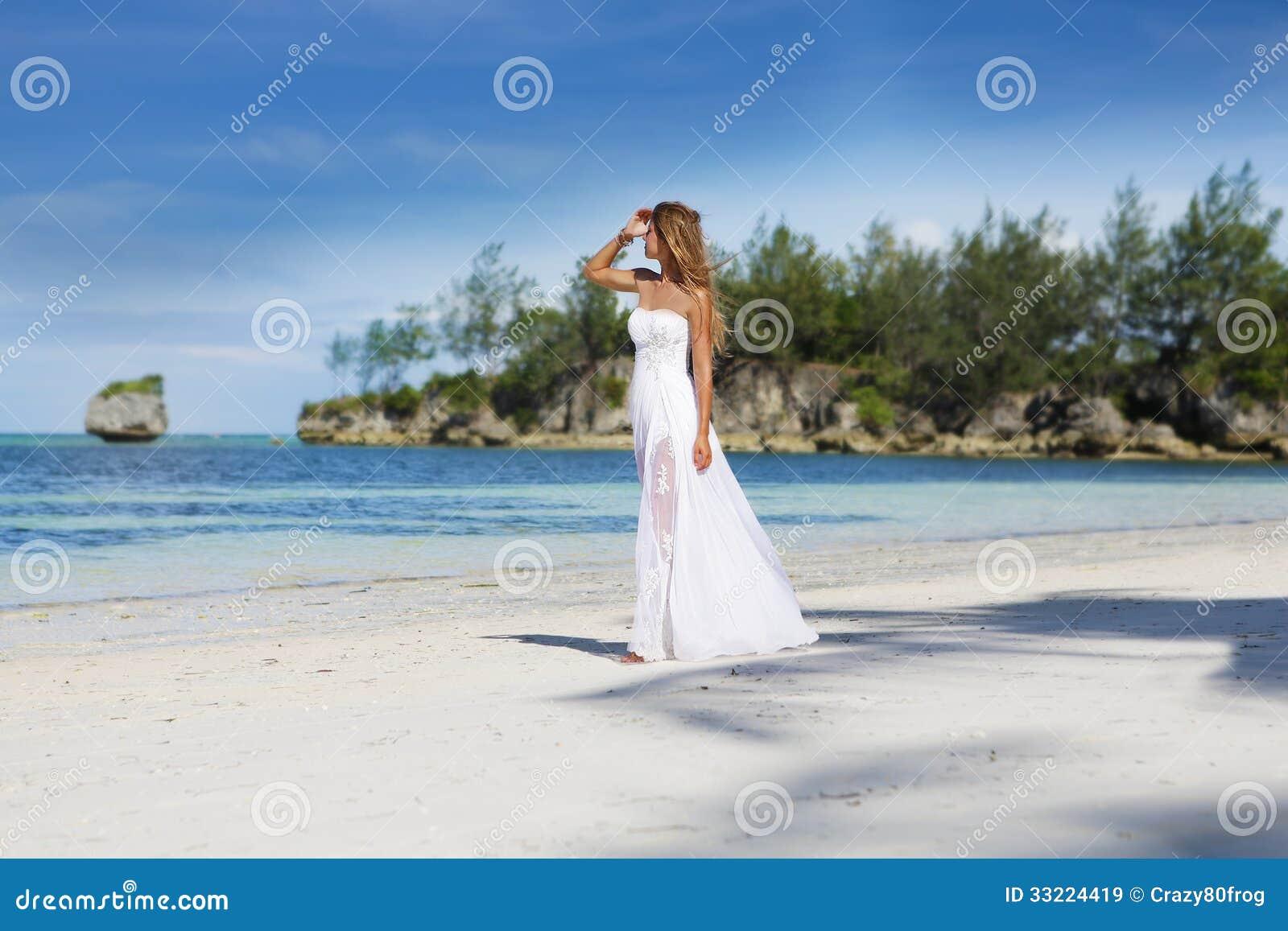 Jeune belle femme dans la robe de mariage sur la plage for Robes de mariage pour la plage