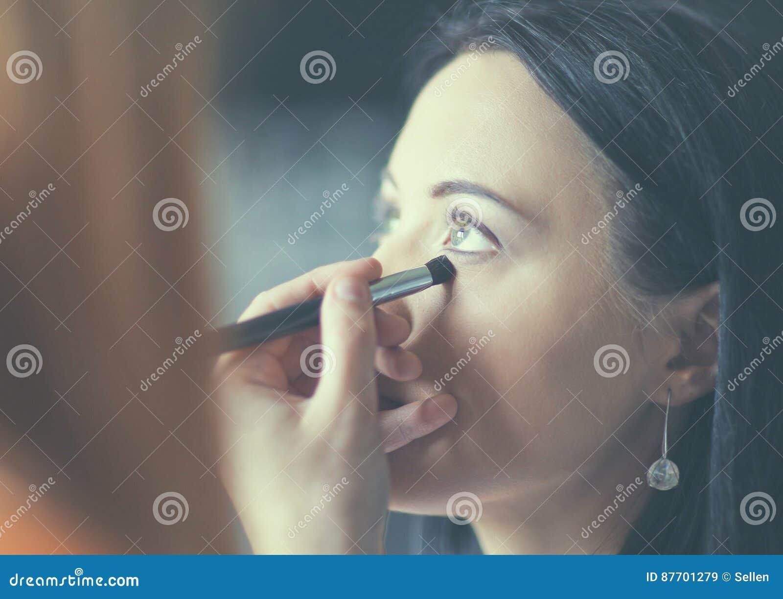 Jeune belle femme faisant le maquillage près du miroir, se reposant au bureau
