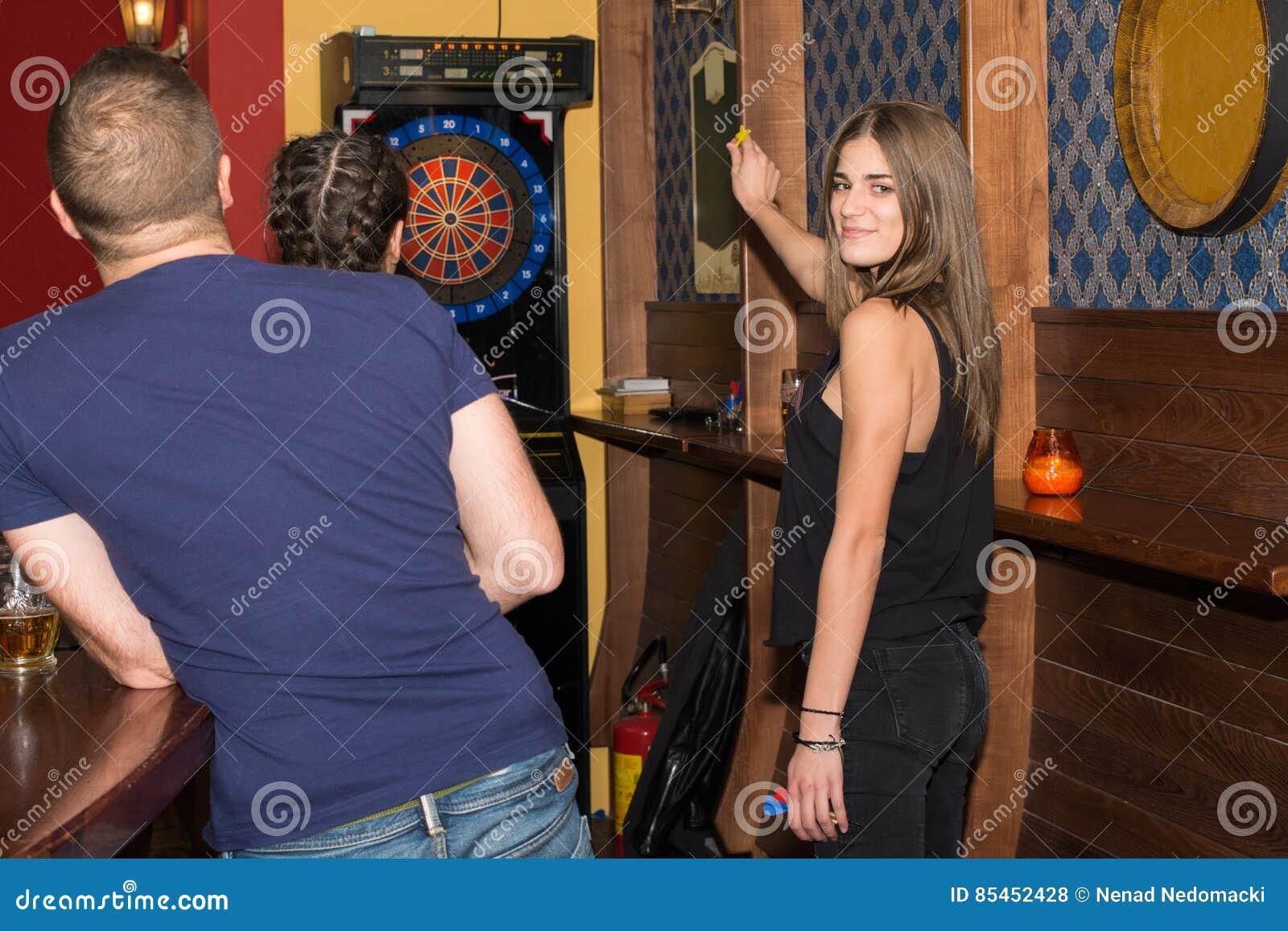Jeune belle femme jouant des dards dans un club