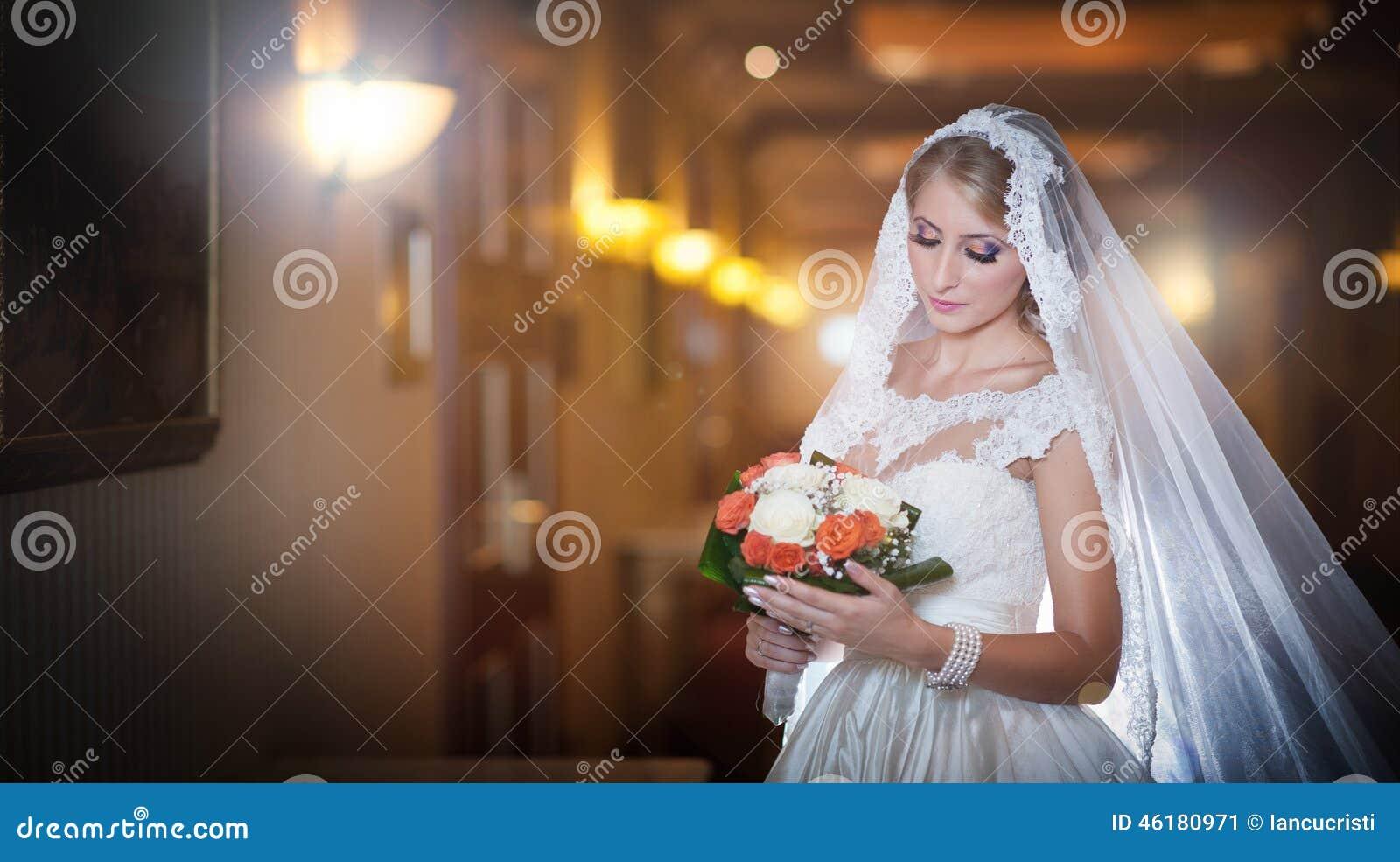 Jeune belle femme luxueuse dans la robe de mariage posant dans l intérieur luxueux Jeune mariée avec le long voile tenant son bou