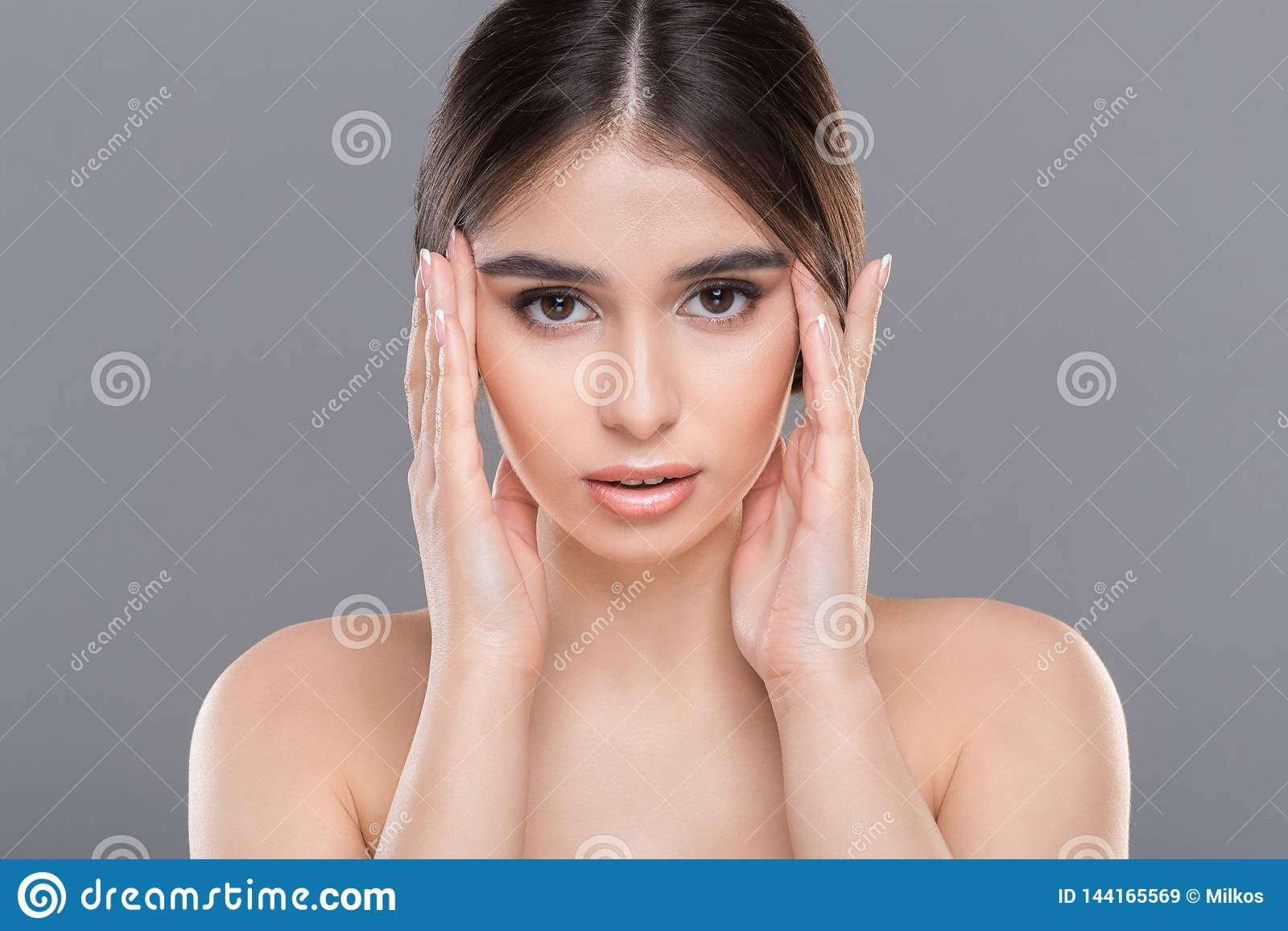 Jeune belle femme massant son plan rapproché de visage