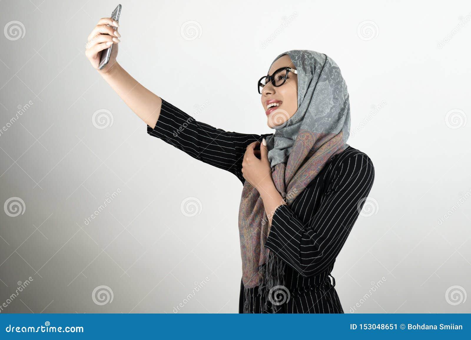 Jeune belle femme musulmane de sourire en verres portant le hijab de turban, smartphone de participation de foulard tirant un sel