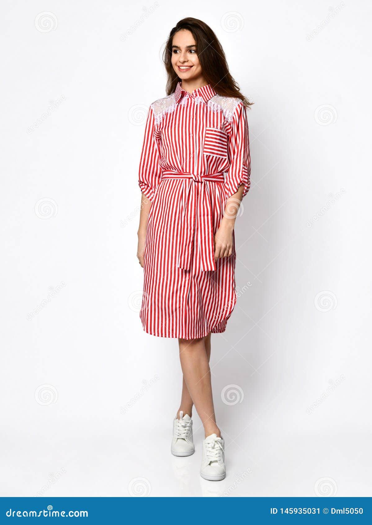 Jeune belle femme posant dans la nouvelle robe rouge-rose de mode de rayures sur le plein corps de hautes collines sur un blanc