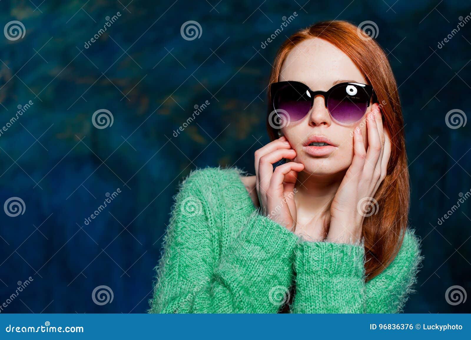 Jeune belle femme rousse dans des lunettes de soleil