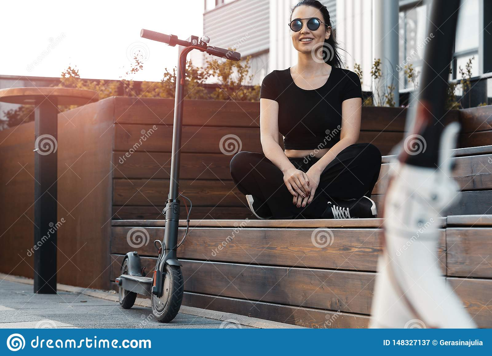 Jeune belle femme s asseyant sur le banc pr?s du scooter ?lectrique de coup-de-pied