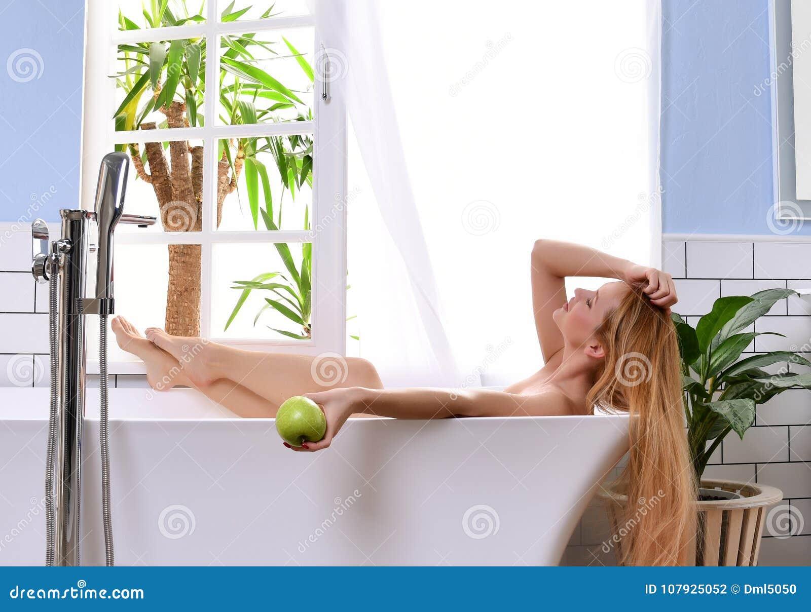 Jeune belle femme se situant dans la baignoire et presque prenant la fenêtre ouverte de salle de bains de bain