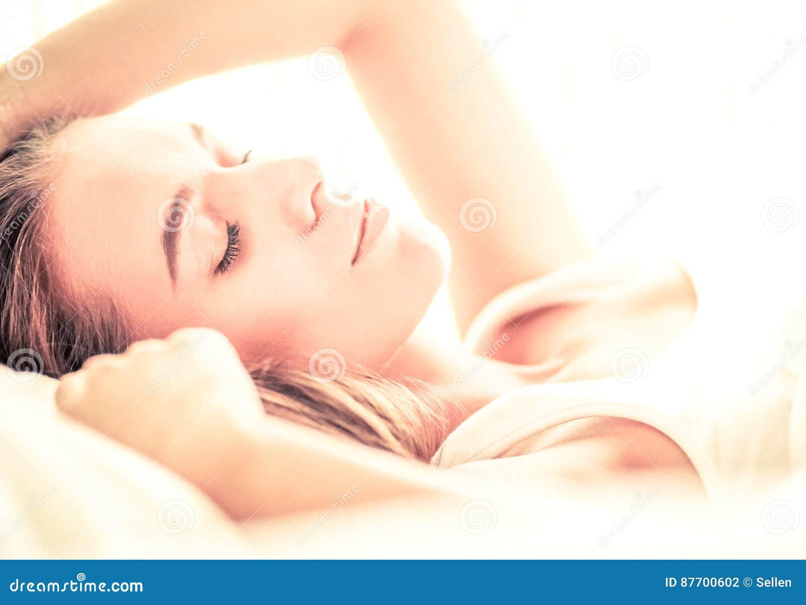 Jeune belle femme se situant dans le lit à la maison