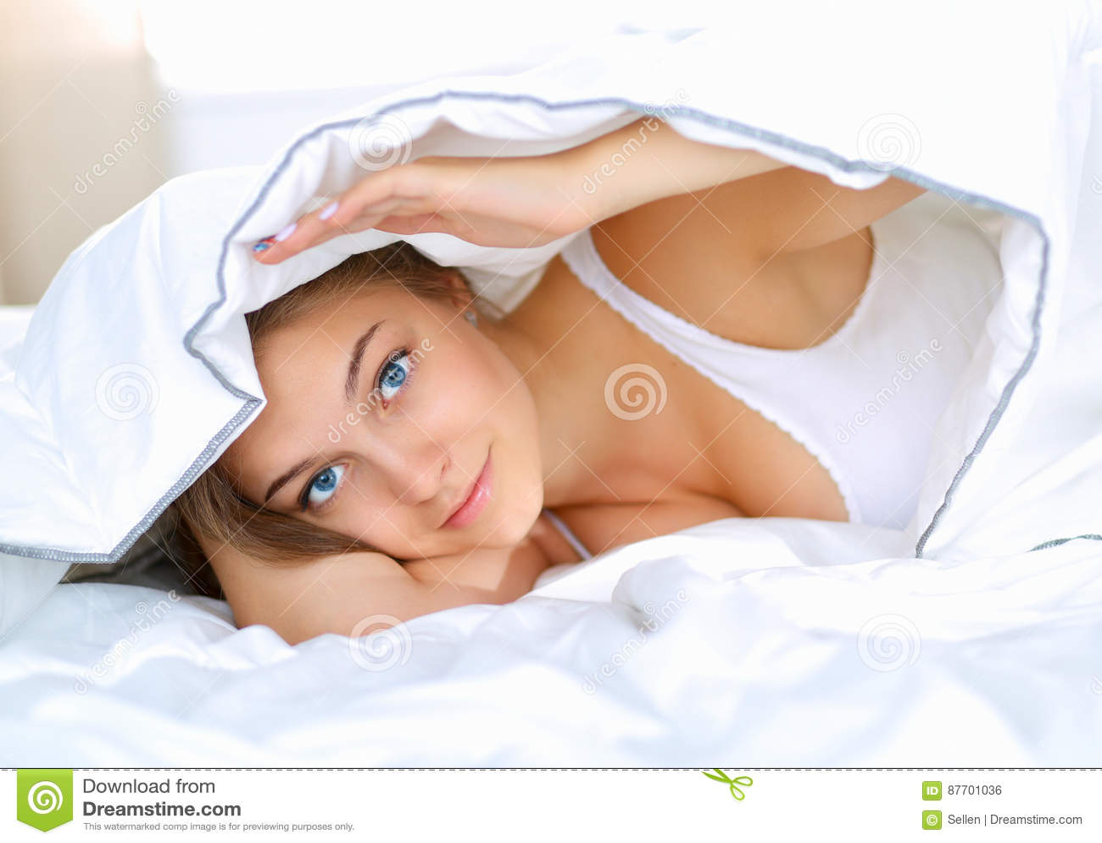Jeune belle femme se situant dans le lit sous la couverture