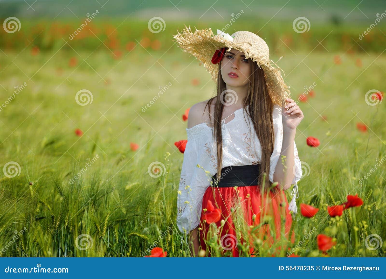 Jeune belle femme sur le gisement de céréale avec des pavots