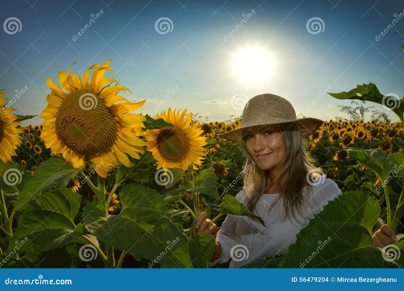 Jeune belle femme sur le gisement de floraison de tournesol
