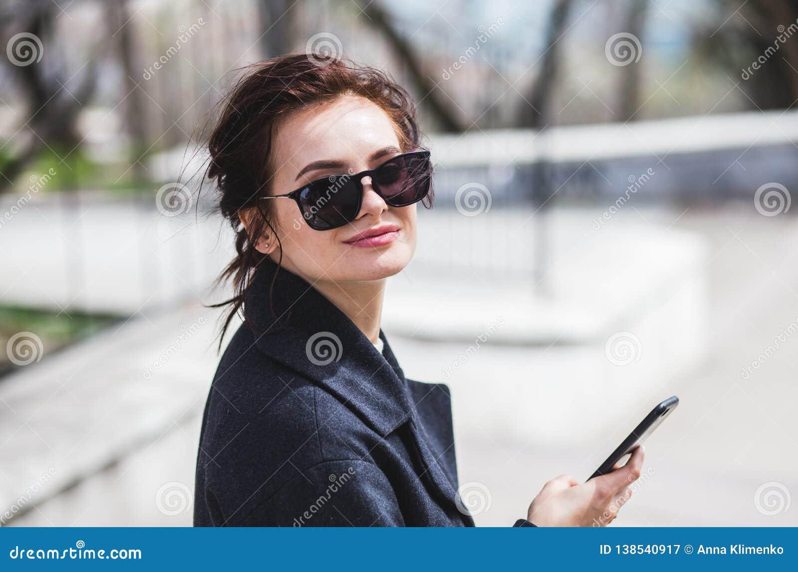 Jeune belle fille élégante de brune dans des lunettes de soleil regardant la caméra tenant son smartphone dans la rue au printemp