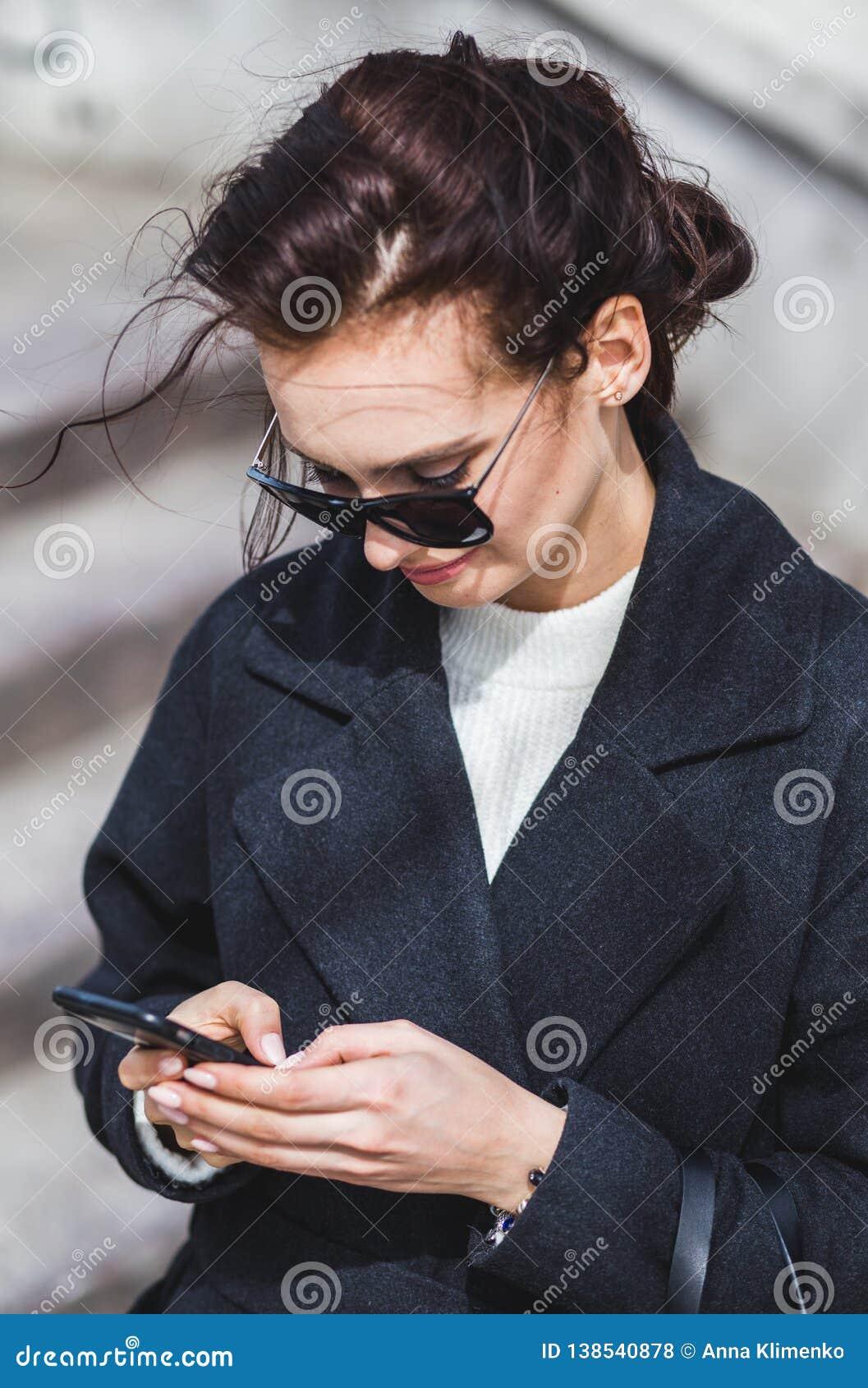 Jeune belle fille élégante de brune dans des lunettes de soleil regardant le smartphone, marchant sur la rue