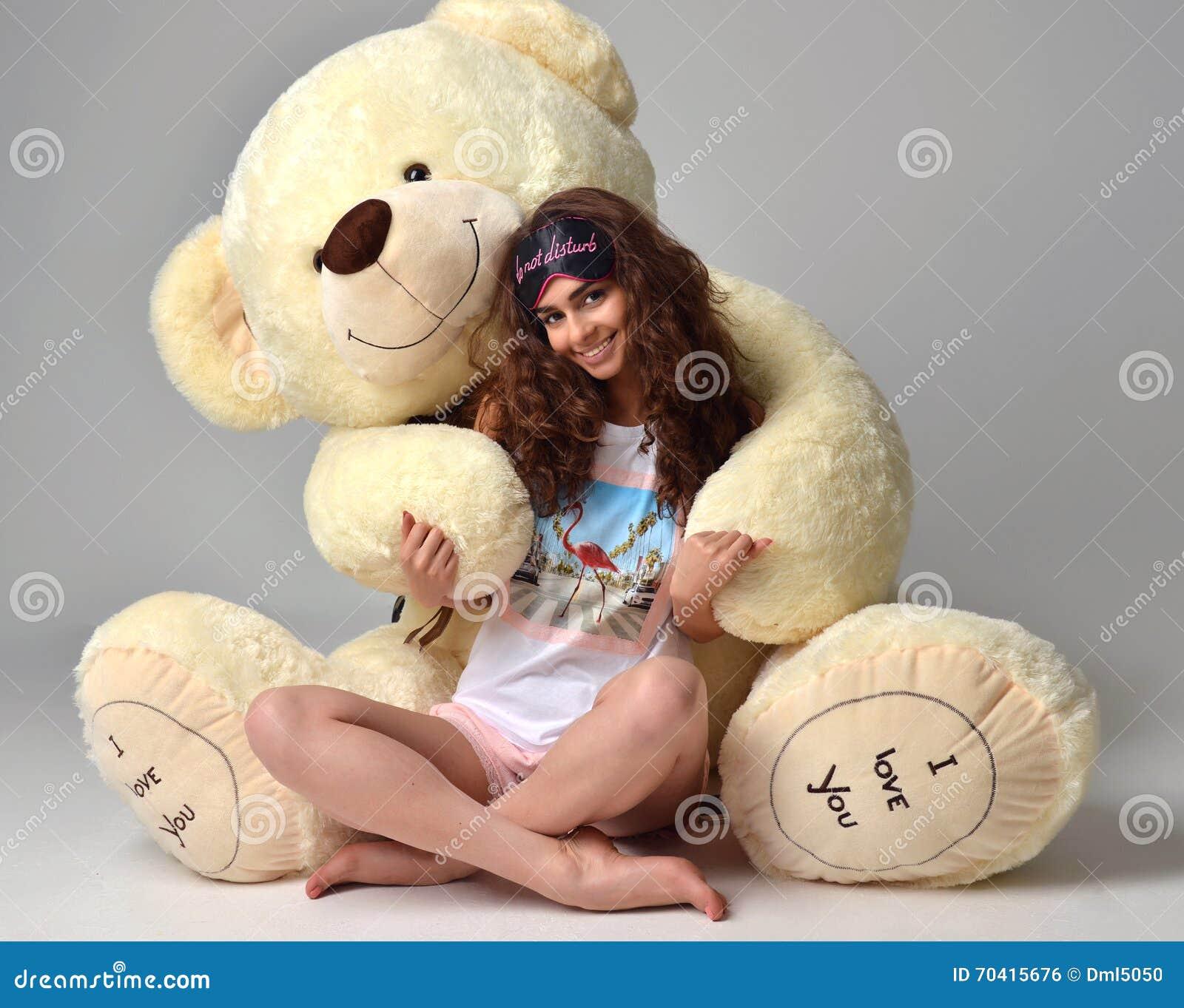 Jeune belle fille étreignant le smili heureux de grand de nounours jouet mou d ours