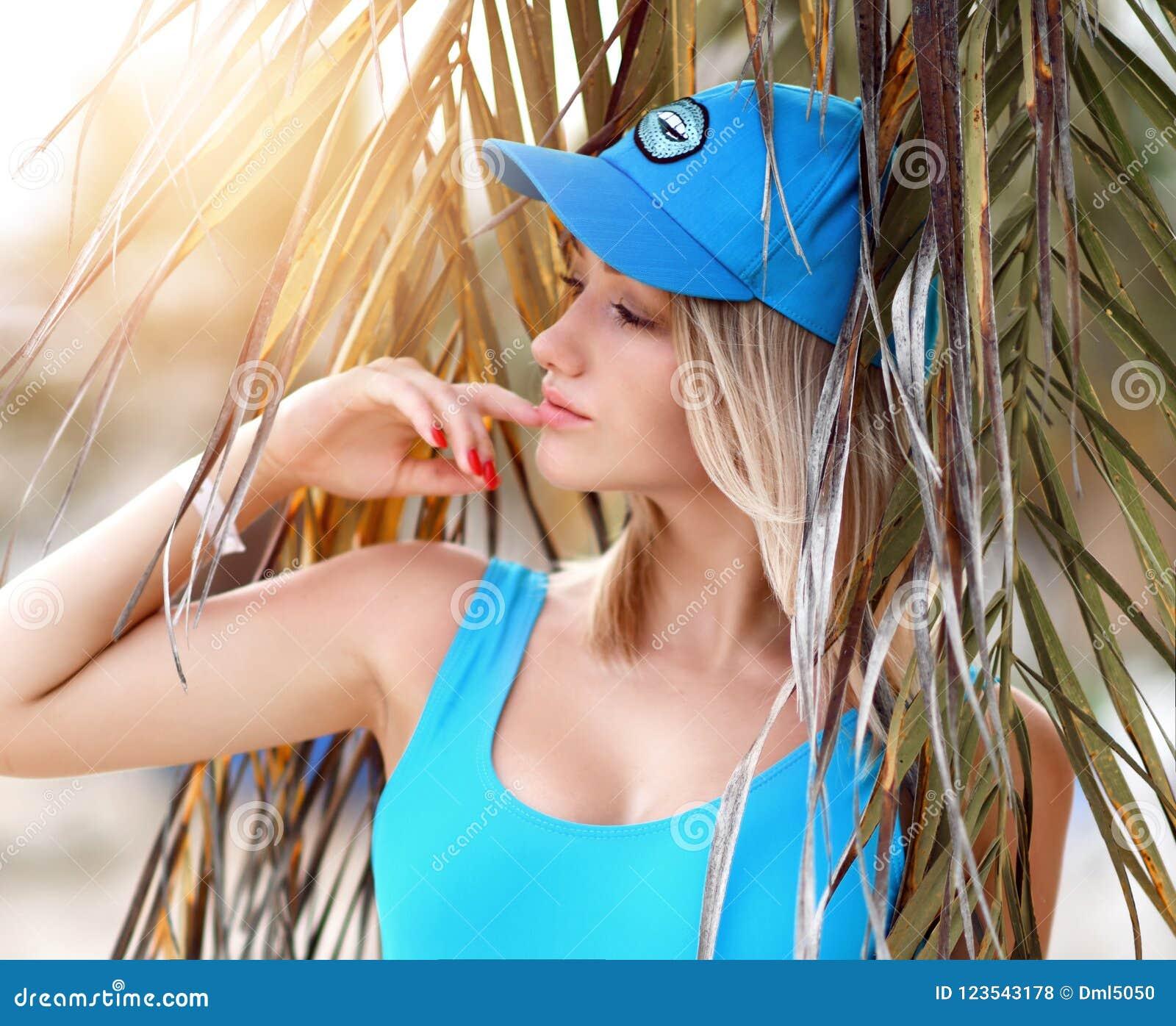 Jeune belle fille blonde posant dans la station de vacances tropicale de forêt de palmier dans le gilet et le chapeau sexy bleus