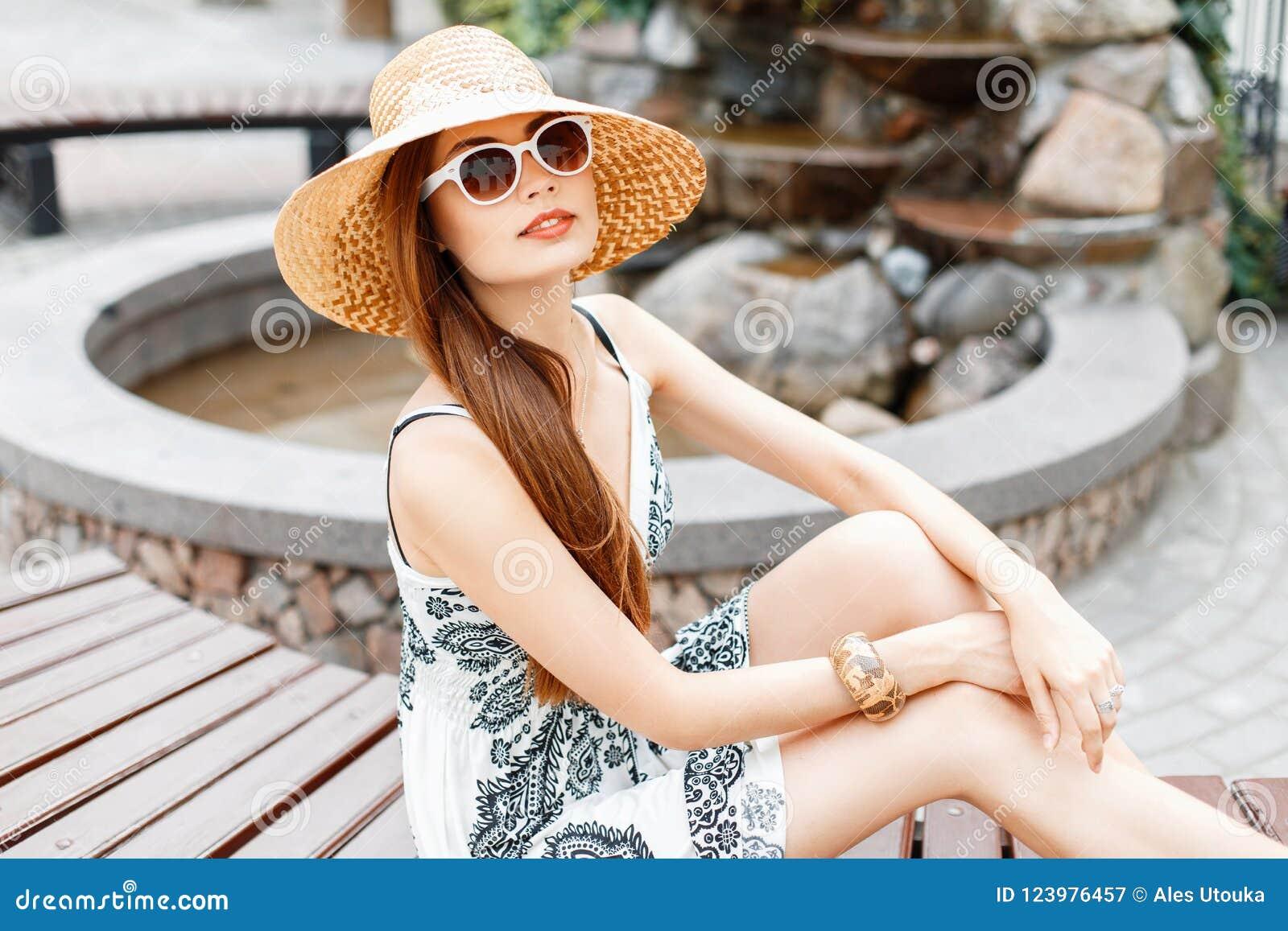 Jeune belle fille dans les lunettes de soleil et le chapeau de paille presque se reposant