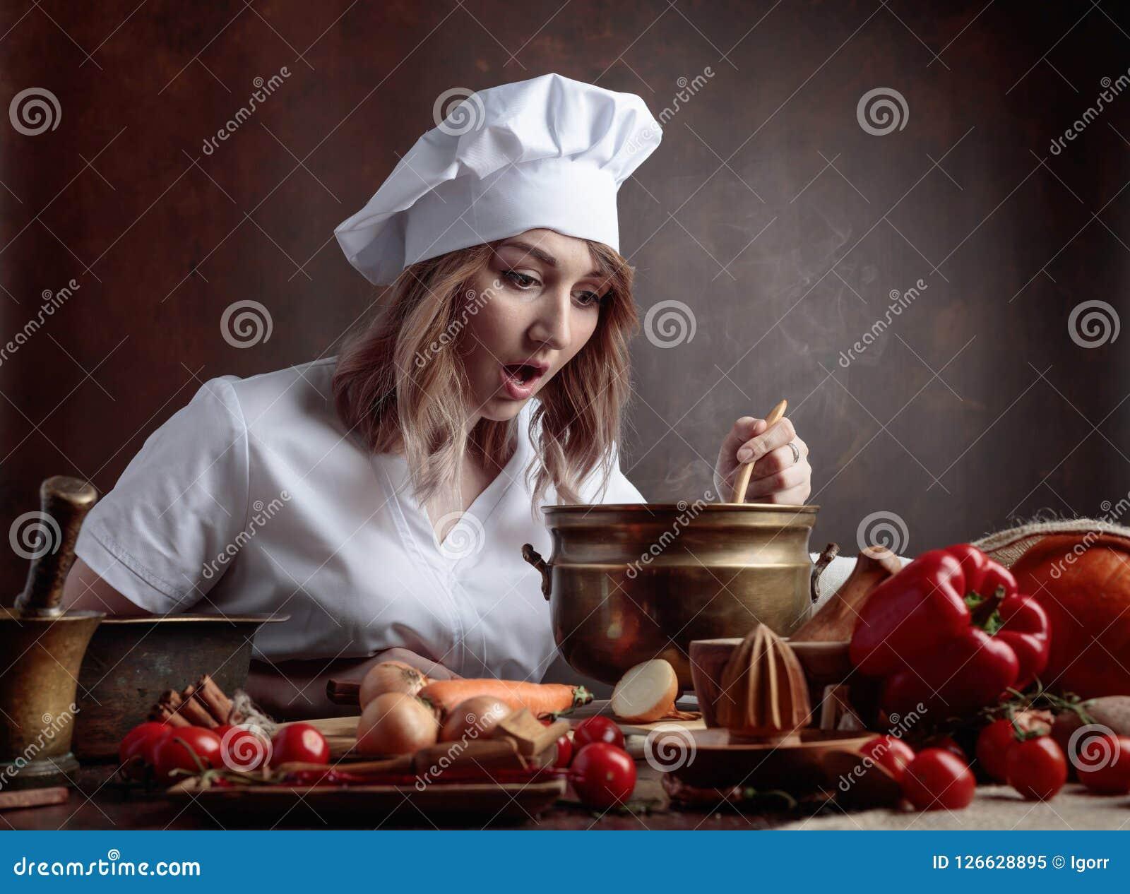 Jeune belle fille dans un uniforme de chef avec la vieille casserole en laiton et le W