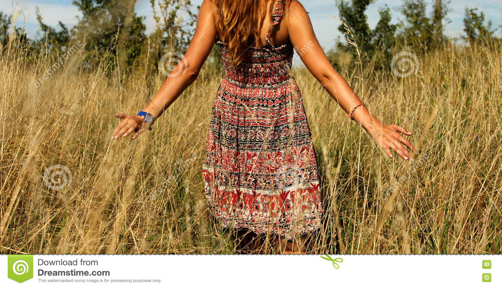 Jeune belle fille marchant dans le champ et la main de courses par la haute herbe sèche à l été