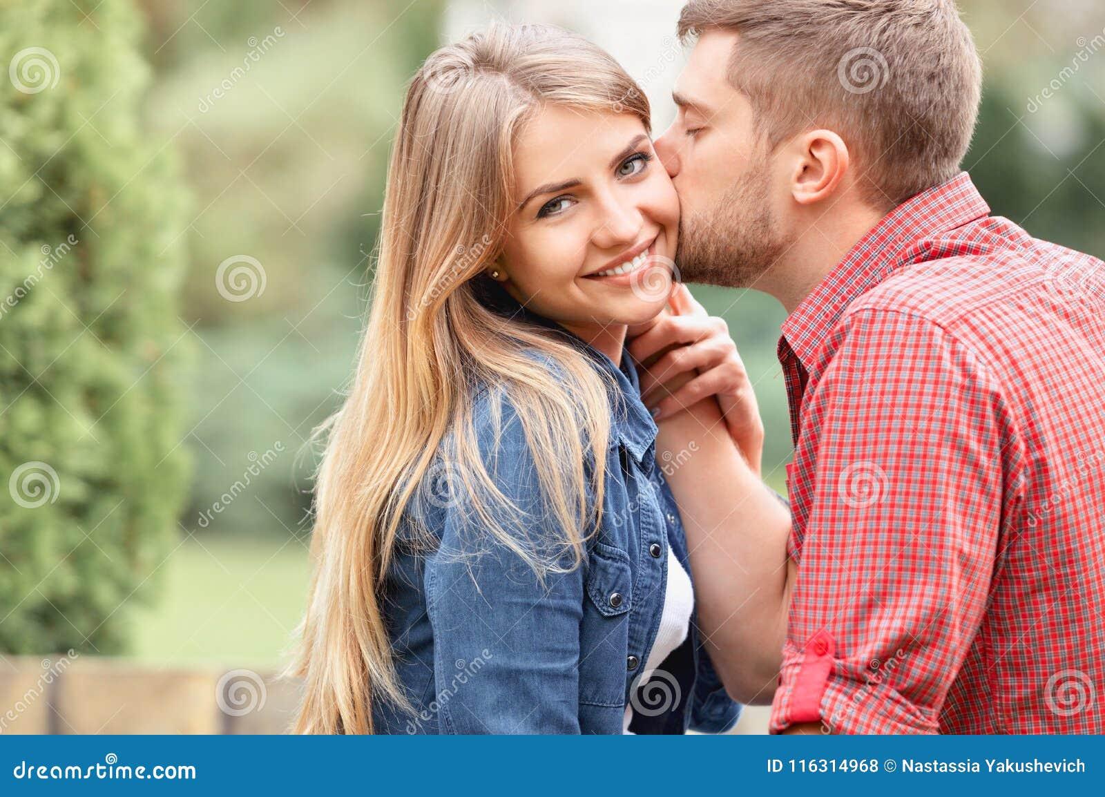 Jeune belle fille regardant fixement l appareil-photo tout en étant embrassé