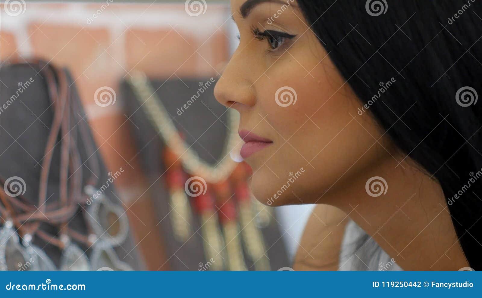 Jeune belle fille regardant le collier sur l étalage dans le magasin de bijoux