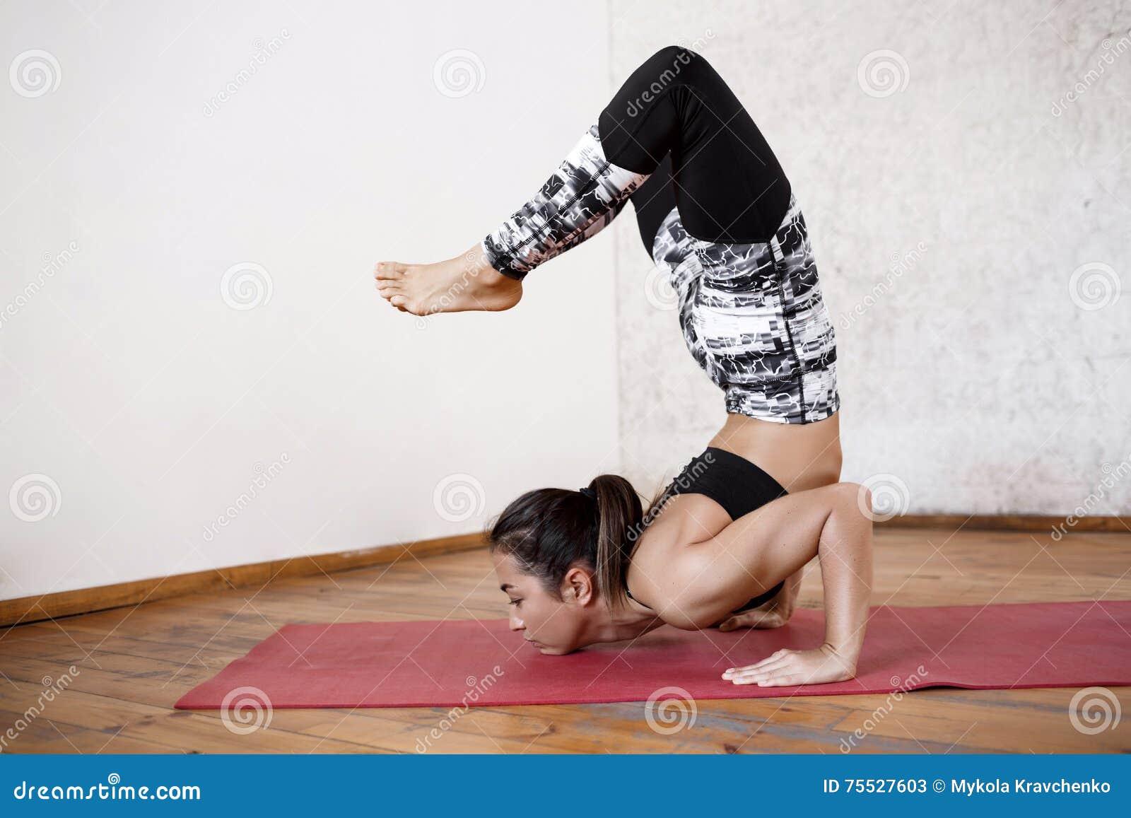 Jeune belle fille sportive pratiquant des asanas d intérieur de yoga Appui  renversé avancé de scorpion 2f43a34065c