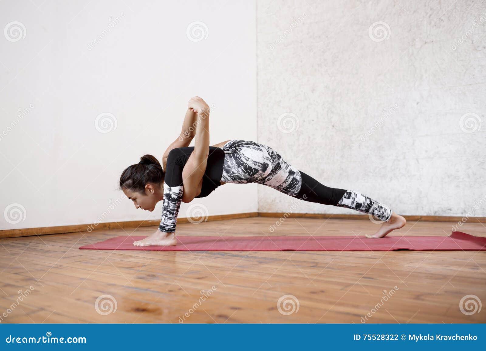 Jeune belle fille sportive pratiquant des asanas d intérieur de yoga sur le  tapis rouge Plancher en bois et fond blanc de mur ea10339bae3