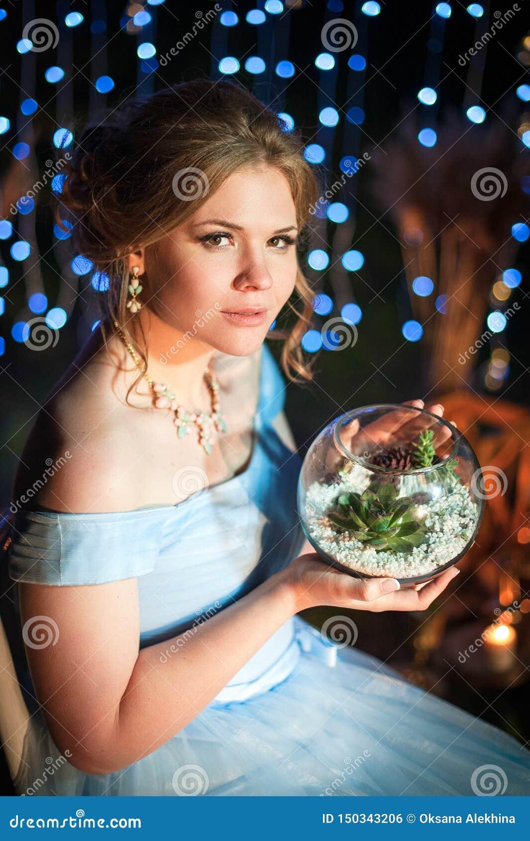 Jeune belle fille tenant un vase avec les usines succulentes sur un fond foncé avec des lumières
