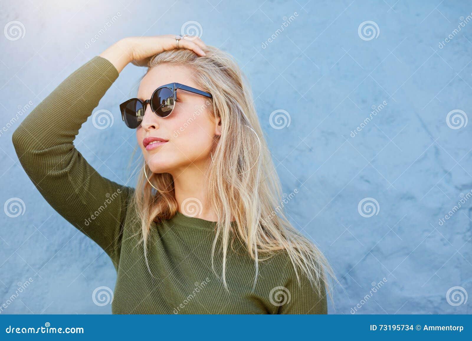 Jeune blonde dans des lunettes de soleil regardant loin