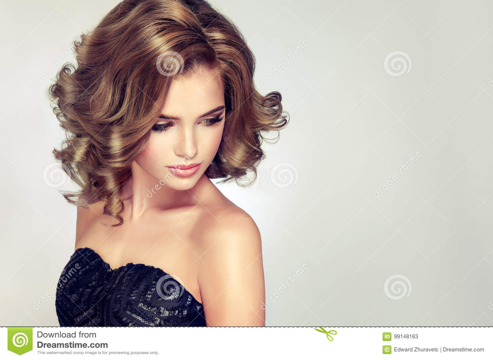 Jeune brune attrayante de femme avec la coiffure onduleuse courte