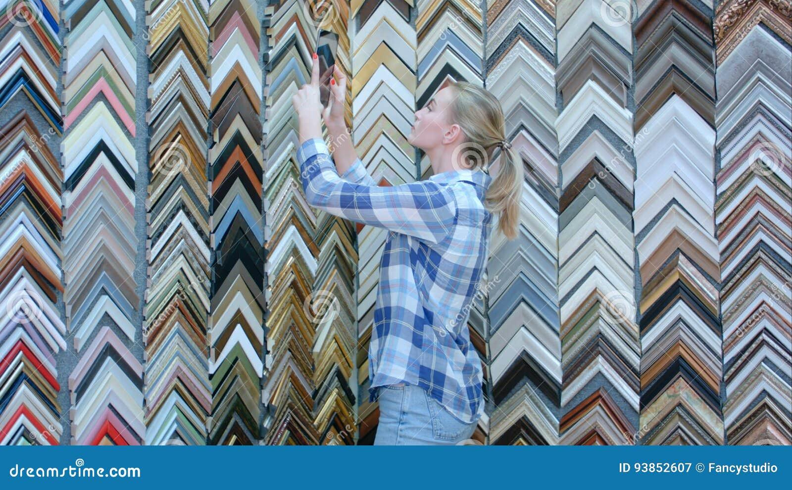 Jeune client féminin songeur recherchant un cadre, choix, prenant la photo avec le comprimé numérique dans l atelier