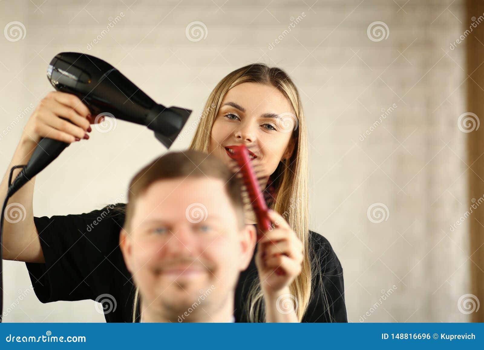 Jeune coiffeur Drying Male Hair par le dessiccateur de coup