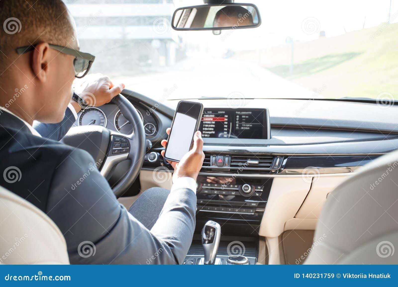 Jeune conducteur d homme d affaires dans des lunettes de soleil se reposant à l intérieur de la conduite utilisant l appli de nav