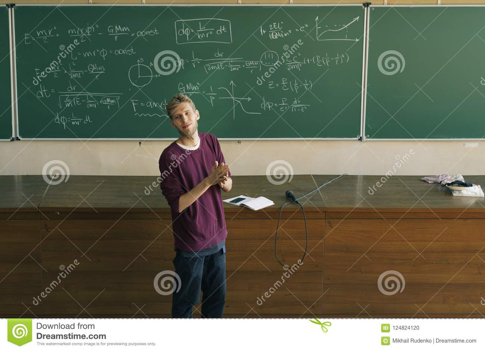 Jeune conférencier masculin dans les applaudissements de salle de conférences avec le tableau noir à l arrière-plan
