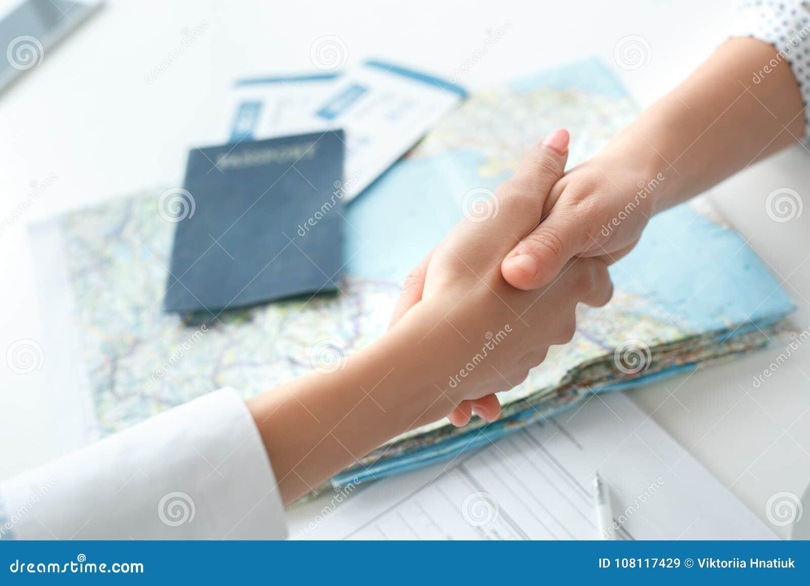 Jeune consultant en matière féminin d agent de voyage à l agence de visite avec une poignée de main de client