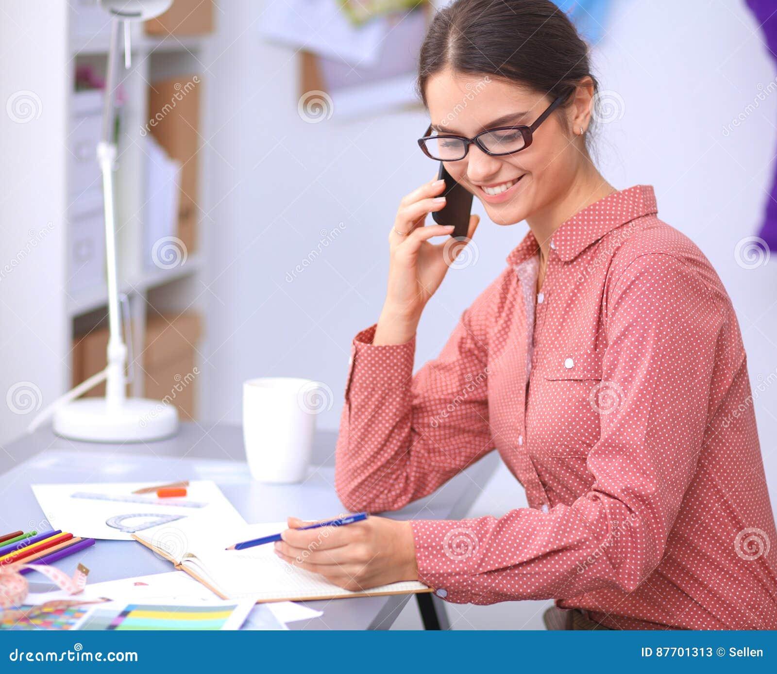 Jeune couturier féminin attirant travaillant au bureau, dessinant tout en parlant sur le mobile
