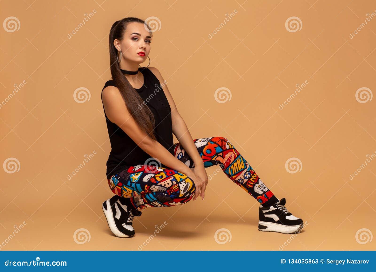 Jeune danseur féminin sur le fond de studio Jeune fille moderne de danseur de style s asseyant sur le plancher dans le studio