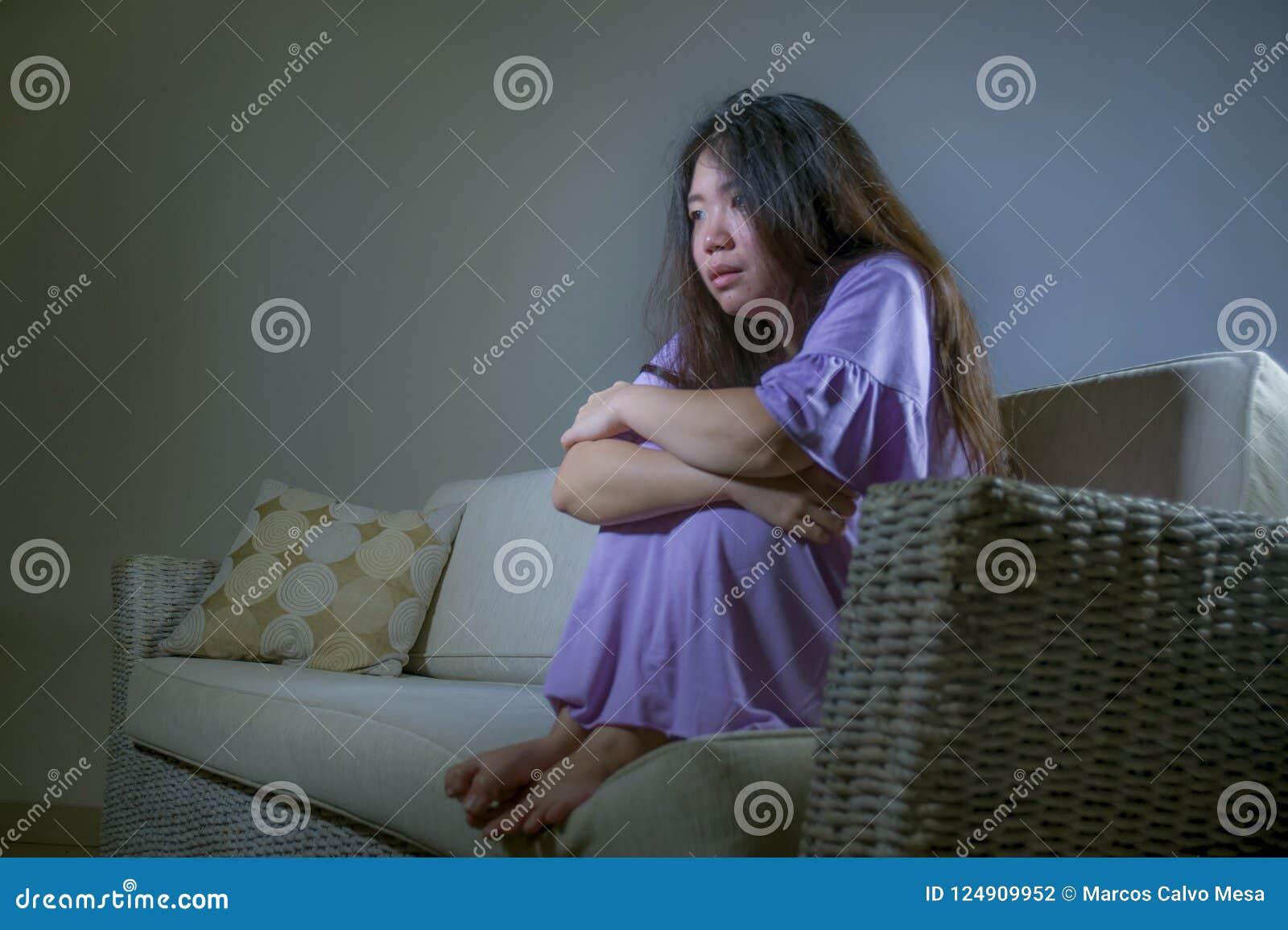 Jeune divan coréen asiatique triste et déprimé de sofa de femme à la maison pleurant feeli de souffrance désespéré et impuissant