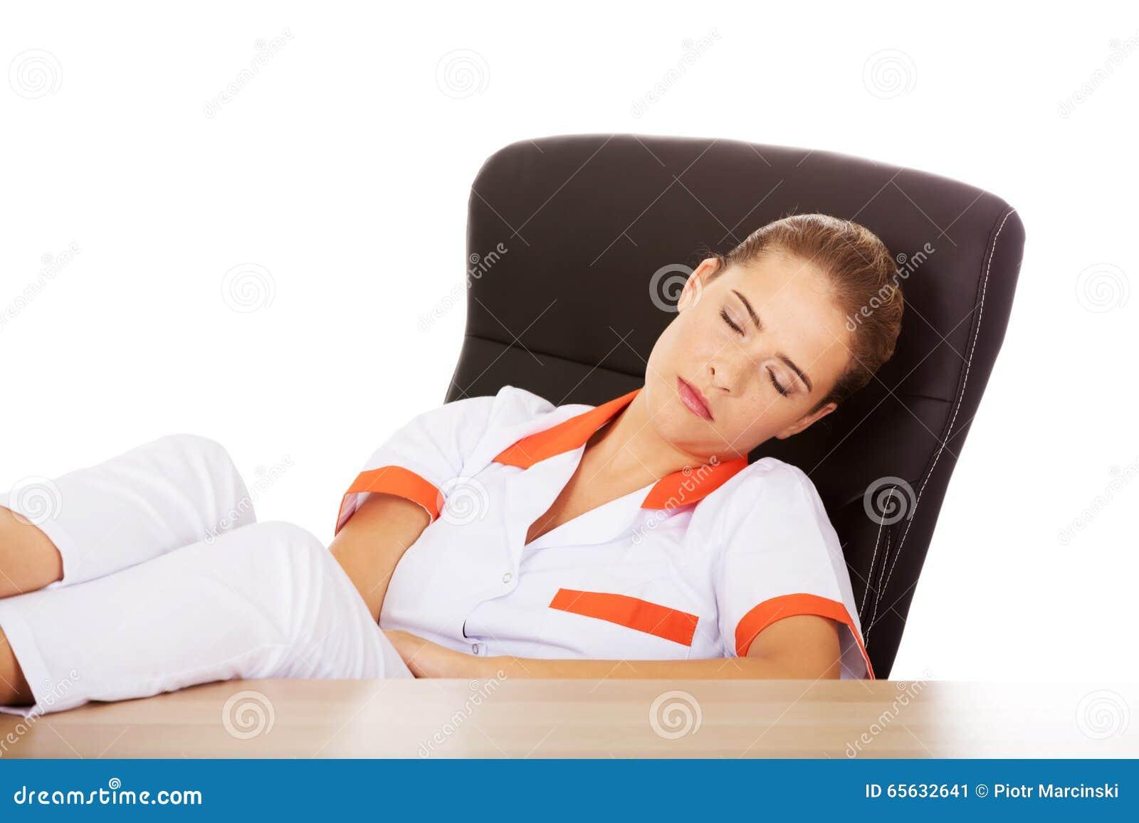 Jeune docteur féminin fatigué dormant avec des jambes sur le bureau